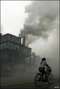Cyclist riding past chimneys emitting thick smoke (AFP)