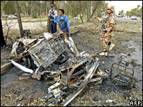 Police inspect the wreckage of a car in western Baghdad