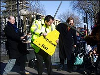 Mark McGowan dressed up as a traffic warden and being beaten with sticks