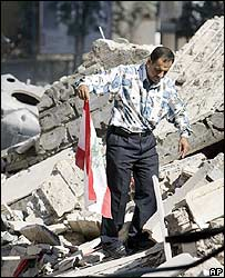 A Lebanese man walks to place a Lebanese flag on the rubble of a collapsed building in Beirut