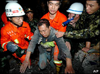 Rescuers help a man from a collapsed building in Wenzhou