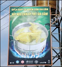 Sign on a Vietnamese street warning people to cook chicken properly before eating it