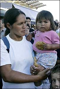 Mother with child eating fritter from the soup kitchen