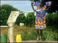África, niño obtiene agua de un grifo.