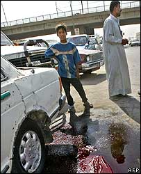 Bystanders at the scene of a Baghdad roadside bombing  12 Aug