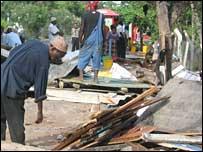 A street vendor picks over the remains of his kiosk in Dar es Salaam, Tanzania