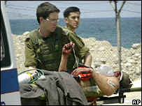 Israeli soldiers carry a wounded comrade (12 Aug)