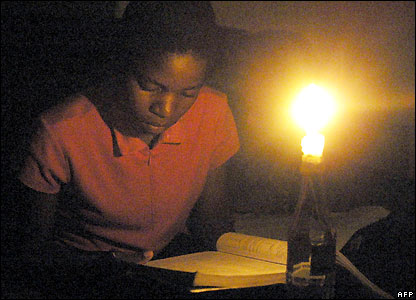 A schoolgirl in Zimbabwe does homework by candlelight on Wednesday