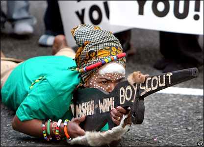 A Jacob Zuma supporter lies on the floor with a wooden replica gun in South Africa
