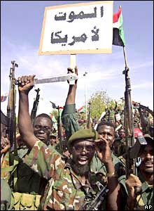 Members of the Sudanese Popular Defence Forces hold up knifes, guns and banners in Khartoum in protest against UN peacekeepers