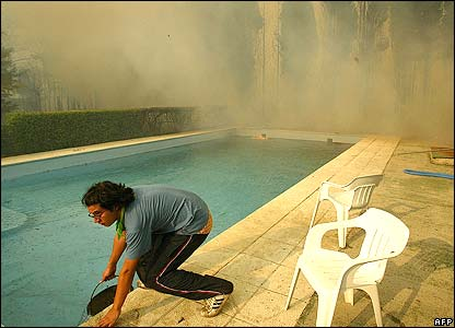 A man uses water from a swimming pool to fight the fires