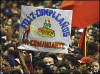 A man holds up a banner wishing Fidel Castro a happy birthday at a concert in Havana