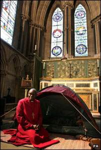 Dr John Sentamu next to his tent