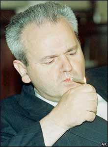 Slobodan Milosevic lights a cigar in his Belgrade office. File photo