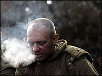 Israeli artilleryman stops for a cigarette between firing shells into Lebanon