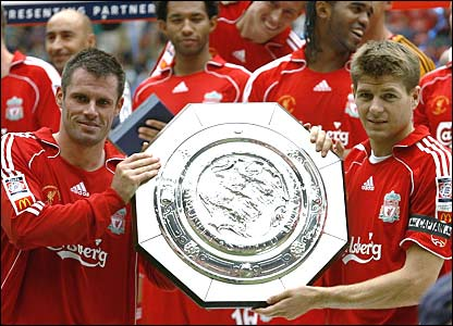 Match captain Jamie Carragher holds the Community Shield aloft with club captain Steven Gerrard