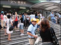 Staff outside Shimbashi station warn passengers that Yurikamome monorail is not in service