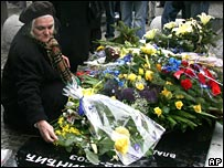 woman lays flowers on a grave of the late Serbian prime minister Zoran Djindjic