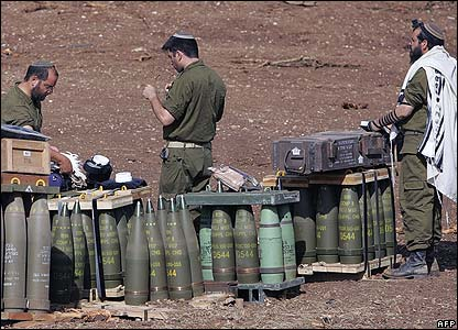 Israeli soldiers stand at an artillery unit