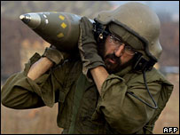 Israeli soldier carries 155mm shells towards a mobile artillery unit, 14 August