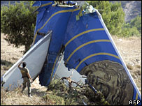 Policeman looks at the tail of the Helios plane at the crash site