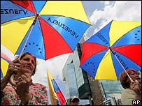 Opposition supporters with umbrellas bearing the old Venezuelan, seven-star flag