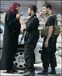Hezbollah militants talk to a woman in Beirut's Shia Muslim stronghold