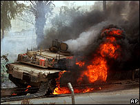 US tank burns after bomb attack in Baghdad on 10 March - the crew escaped unhurt