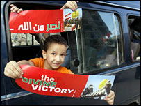 Lebanese boys return to homes in southern Beirut, holding Hezbollah posters