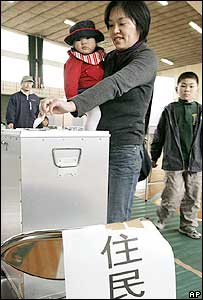 A resident drops a voting paper into a ballot box in a plebiscite at Iwakuni, southern Japan, on Sunday March 12, 2006.