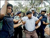 Police take away an opposition protester in Dhaka