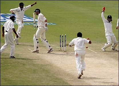 Mahendra Dhoni (r) celebrates after stumping Steve Harmison