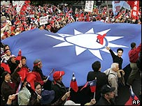 Opposition party supporters march with a giant Taiwan Nationalist Party flag and shout slogans denouncing Chen's termination of a government committee responsible for unification, March 12, 2006.