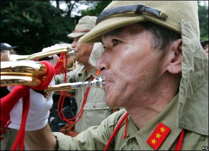 An elderly Japanese man in military uniform blows a trumpet to pay respects to the war dead