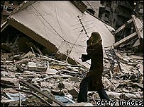 Woman walks through rubble in Beirut, 14 August 2006