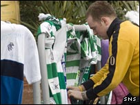 A Celtic fan places a tribute outside the stadium