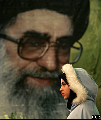 A woman walks past a poster of Ayatollah Ali Khameni