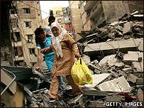 Una mujer camina por escombros