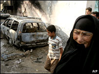 A woman walks past a burnt-out car in Sadr City, Baghdad, after a gun battle, 7 August 2006