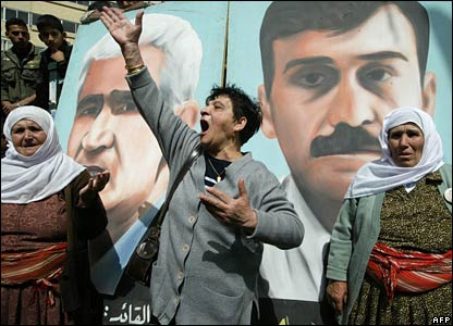 The mother of one of the detainees protests the action in front of a poster of Mr Saadat (on the left)