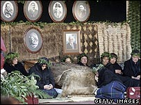Mourners sit beside the body of the late queen in Ngaruawahia, New Zealand
