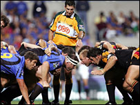 A referee oversees a scrum in the Super 14s competition