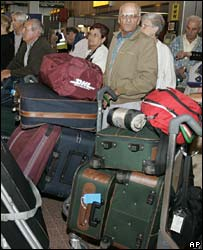 Passengers wait to check in