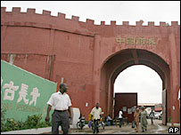 People walk in and out of the China town compound in Lagos, Nigeria, Tuesday, Aug. 1, 2002