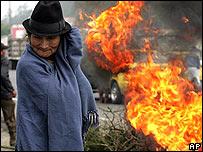 Una indígena ecuatoriana y en el fondo carros incendiados