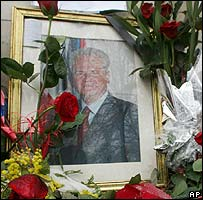Roses are laid on a photo showing Slobodan Milosevic in front of his Socialist party headquarters in Belgrade