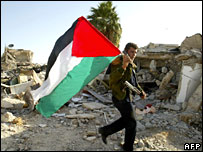 Palestinian security officer holds a flag aloft in the remains of the jail in Jericho