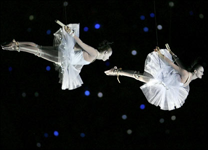 Two ballerinas fly above the stadium