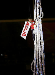 A boy holds a 'help' sign as he stands on elevated rope