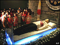 Supporters of the former Philippines president crowd around his glass coffin, in a refrigerated mausoleum